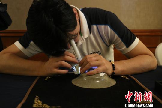 上海收藏爱好者现场用仪器观察瓷器表面。